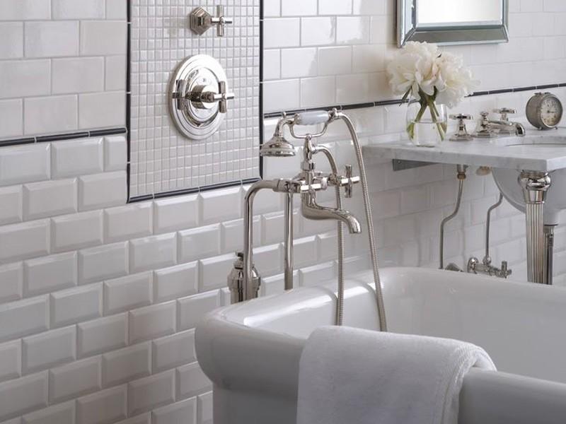 Блестящий смеситель на фоне белой стены из плитки кабанчик