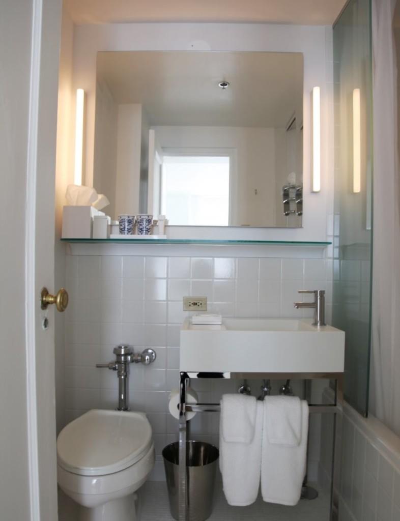 Маленький туалет с большим зеркалом на стене