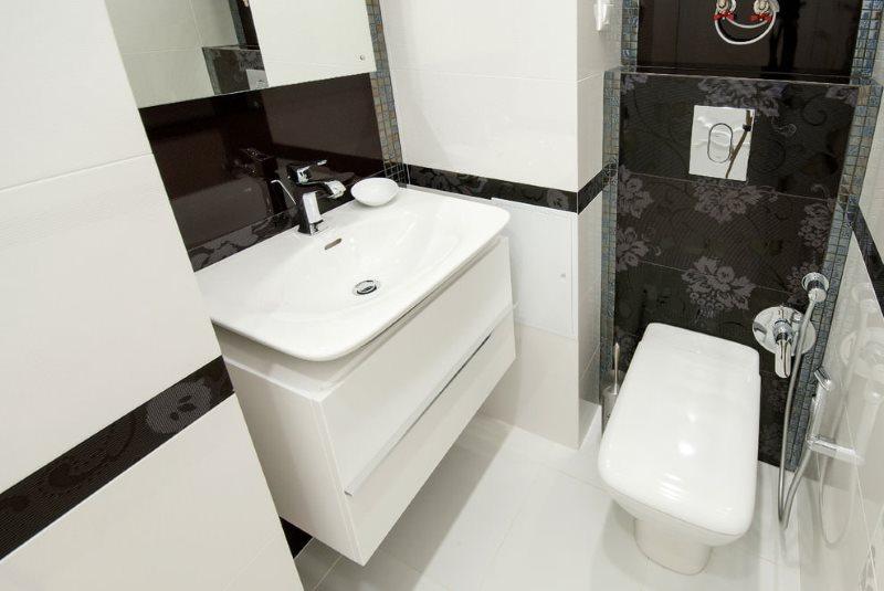 Белая сантехника в туалетной комнате с черной плиткой