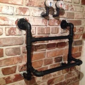 Полотенцесушитель из водопроводных труб на кирпичной стене