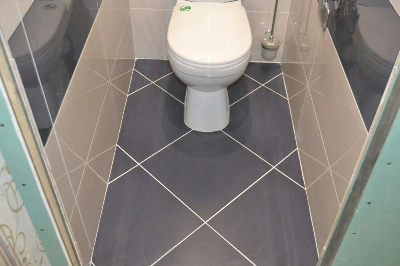 Диагональная укладка серой плитки на полу туалета