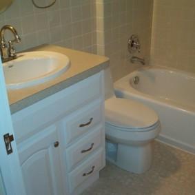 Тумба с умывальником возле двери в ванной комнате