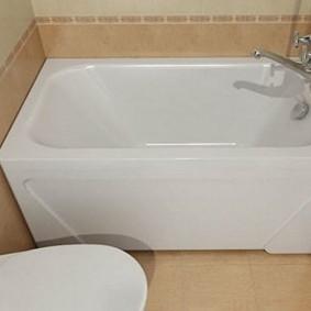 Белая ванна на фоне бежевой плитки