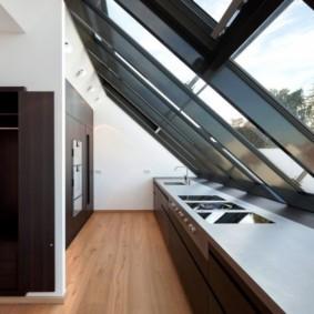 Кухня в мансардном помещении с большими окнами