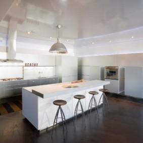 Белая мебель на темном полу кухни