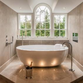 Белая ванна перед окном в загородном доме