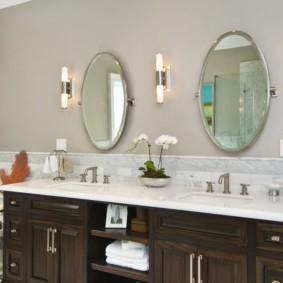 Два овальных зеркала на стене в ванной