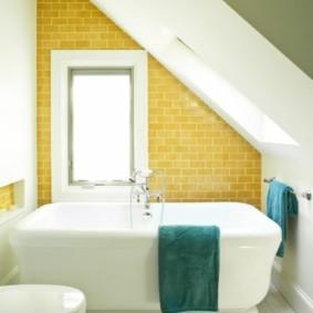 Желтый кафель в ванной со скошенным потолком