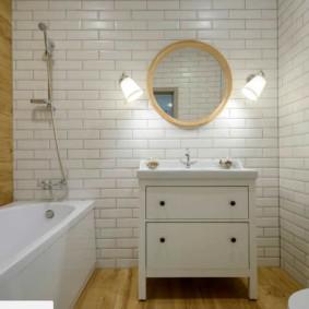 Крулое зеркало на кафельной стене