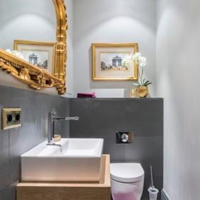 Картина в золотистой рамке на стене туалета