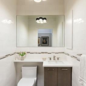 Большое зеркало без рамки над умывальником