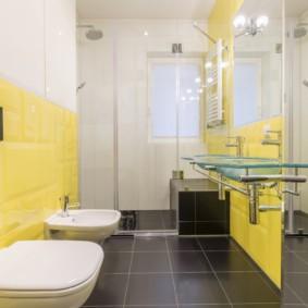 Серый пол в санузле с желтой плиткой на стене