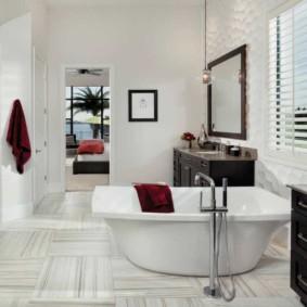 Бардовое полотенце на бортике белой ванной