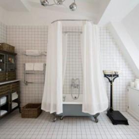 Белые занавески вокруг ванны в мансардном помещении