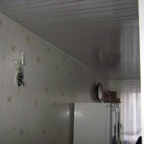 Белый холодильник около стены с отделкой ПВХ-панелями