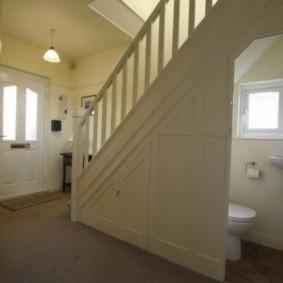 Открытая дверь в туалет под лестницей