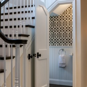 Белая дверь в помещение под лестницей