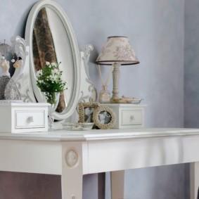 Овальное зеркало на деревянном столике