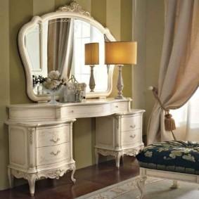 Зеркало с деревянной рамой в спальне классического стиля