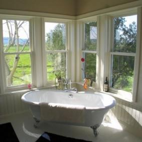 Ванна в комнате с деревянными окнами