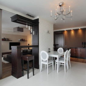 Барная стойка из темного дерева в светлой кухне-гостиной