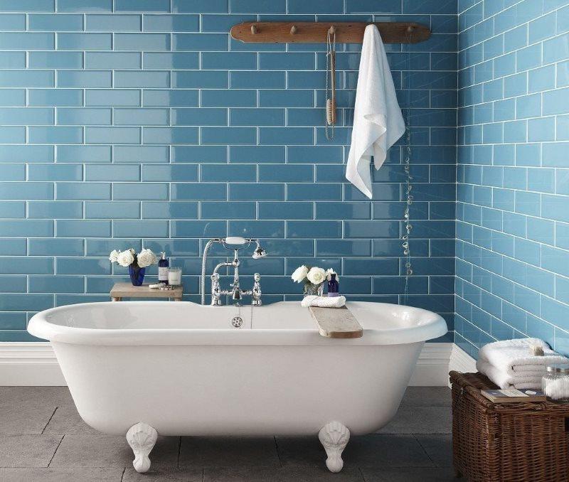 Голубой кабанчик на стене ванной с серым полом