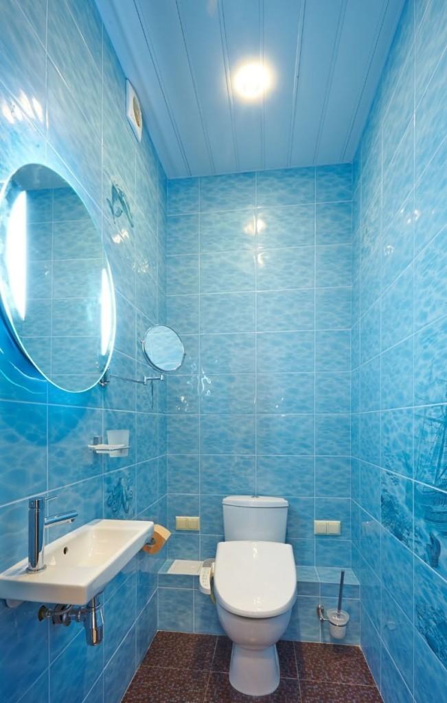 Голубые панели на потолке туалета в городской квартире