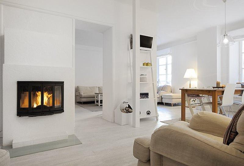 Белая кухня-гостиная с камином в скандинавском стиле