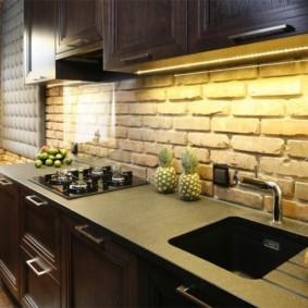 кухня с кирпичной стеной и гарнитуром