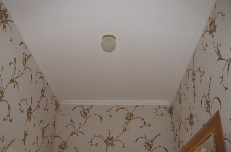 Небольшой светильник на крашенном потолке туалета