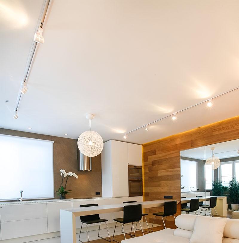 Софиты с направляющими на белом потолке кухни-гостиной