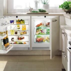 Низкий холодильник под подоконником кухни