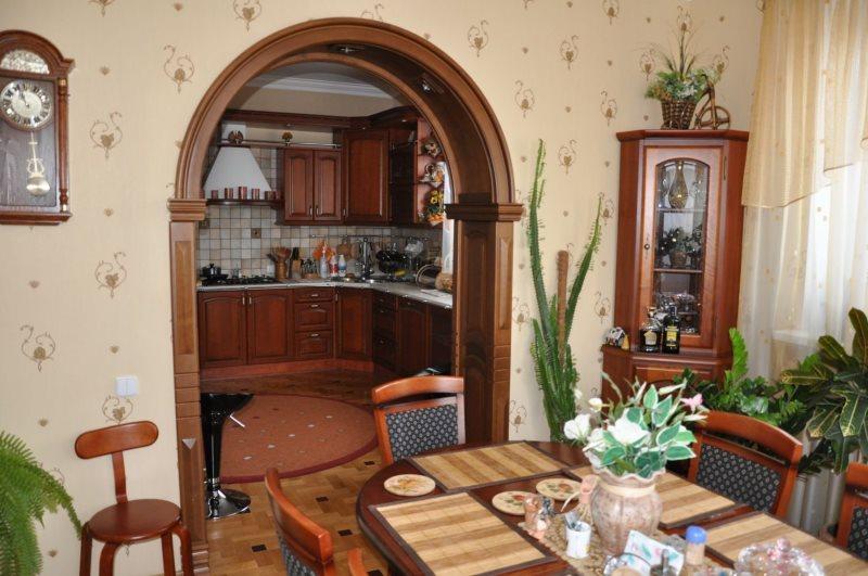 Деревянная отделка арки между кухней и гостиной