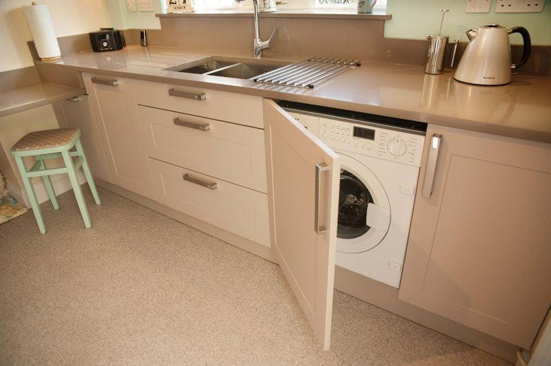 Белая стиральная машина за дверцей кремового цвета