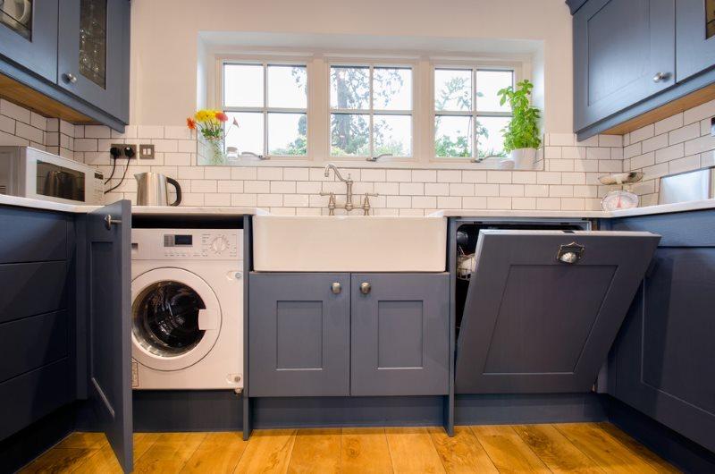 Стиральная машинка за серыми фасадами кухонного гарнитура