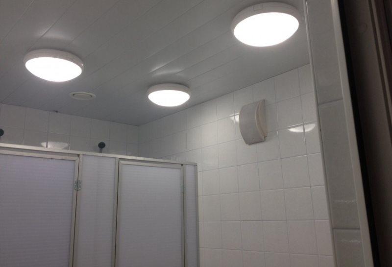 Три светильника накладного типа на потолке из ПВХ-панелей