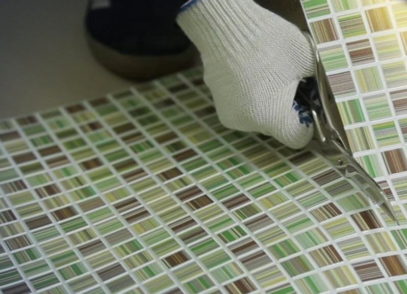 Нарезка листа пластиковой мозаики перед облицовкой стены