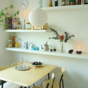 Белые полки над обеденным столом прямоугольной формы