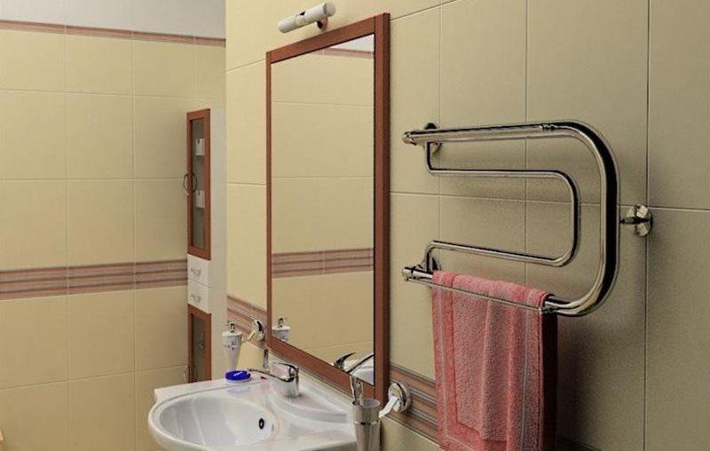 Водяной полотенцесушитель на стене рядом с зеркалом