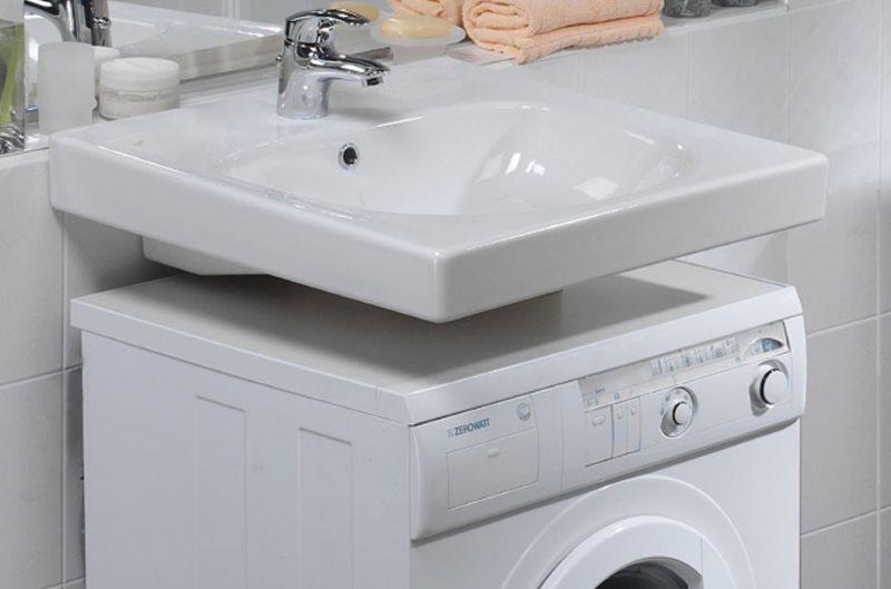 Белая раковина над современной стиральной машиной