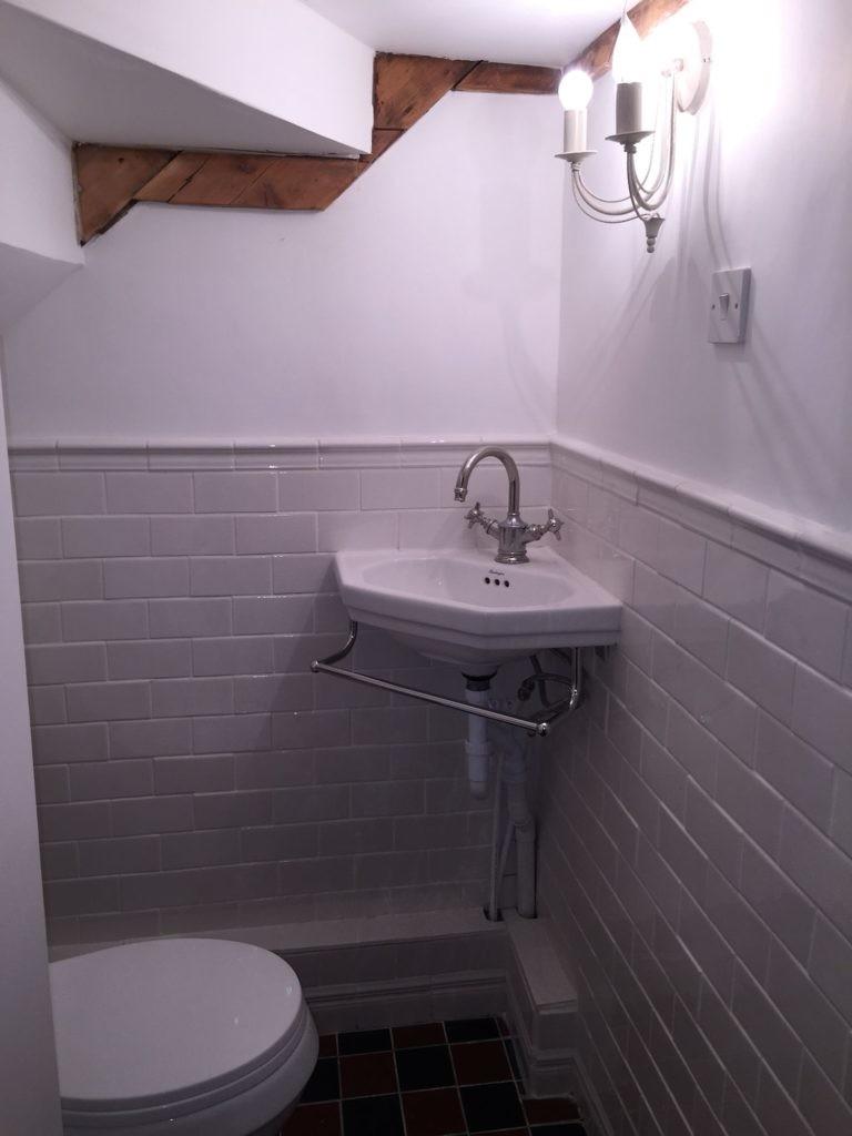 Угловая раковина в туалете под лестницей