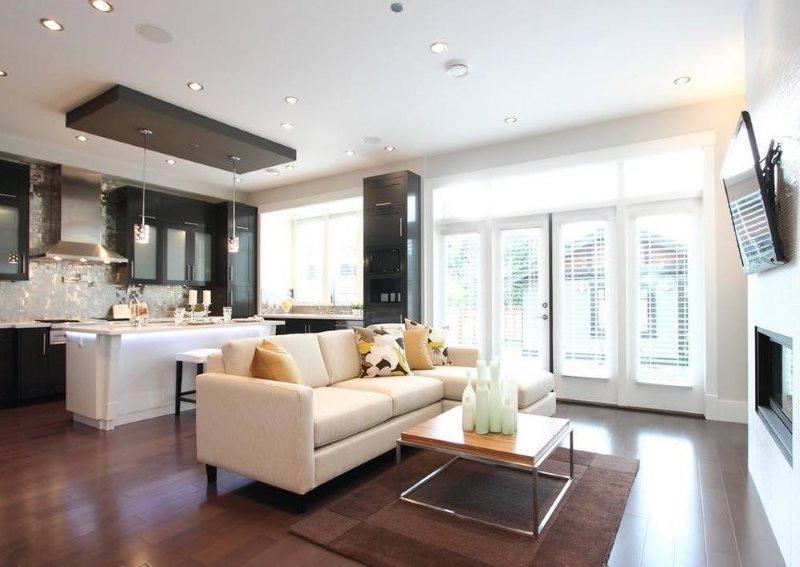 Черный гарнитур в кухне-гостиной с белым диваном