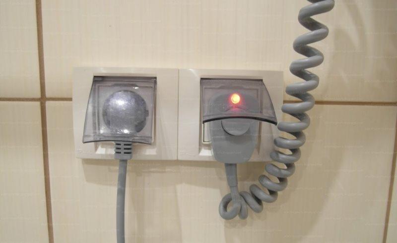 Исправные розетки с защитными крышками на стене ванной комнаты
