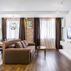 Коричневый диван на дощатом полу