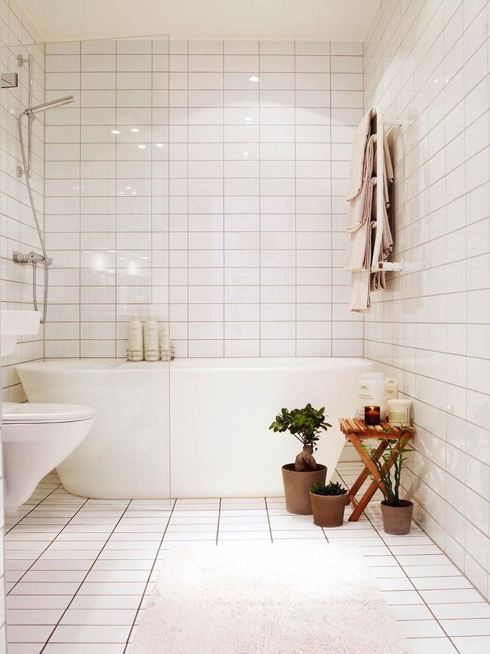 Белая плитка на стене ванной с комнатными растениями в интерьере