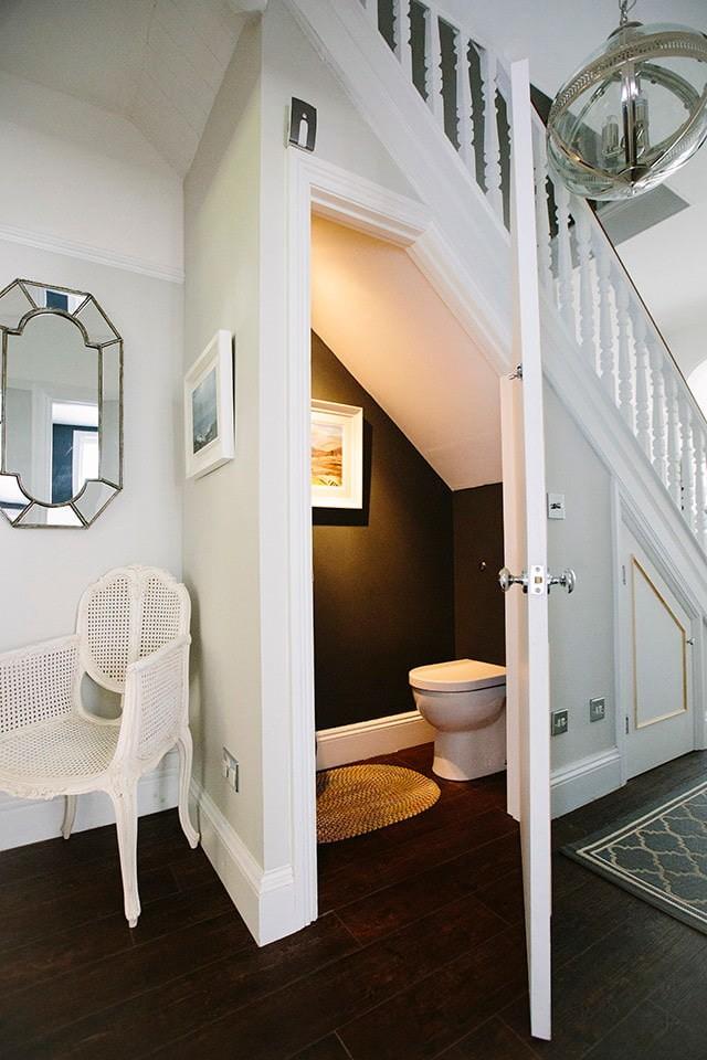 Туалет под маршевой лестницей в деревянном доме
