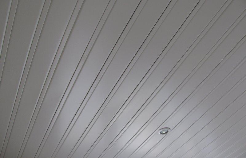 Белая поверхность реечного потолка в ванной комнате