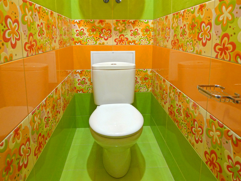 Белый унитаз в туалете с кафельной плиткой яркой расцветки