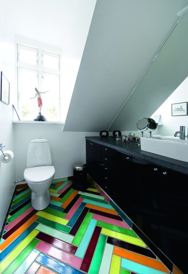 Яркая плитка на полу туалета в мансардном помещении