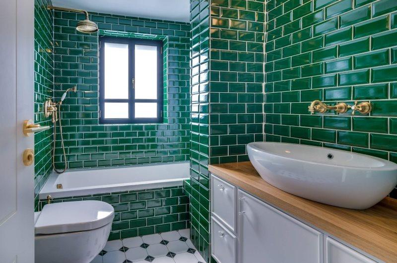 Плитка изумрудного цвета на стенах ванной с окном